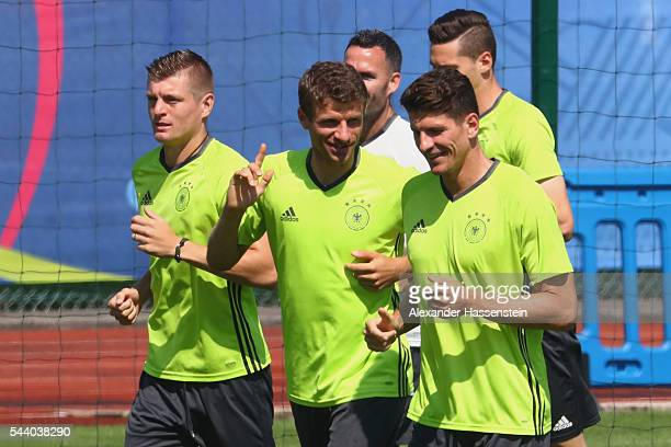 Thomas Mueller of Germany runs with his team mates Toni Kroos and Mario Gomez during a Germany training session ahead of their Euro 2016 quarter...