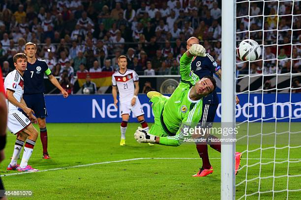 Thomas Mueller of Germany scores their first goal with a header past goalkeeper David Marshall of Scotland during the EURO 2016 Group D qualifying...