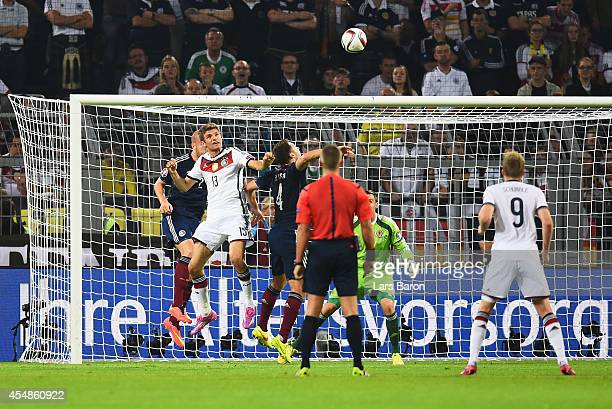 Thomas Mueller of Germany scores their first goal with a header during the EURO 2016 Group D qualifying match between Germany and Scotland at Signal...