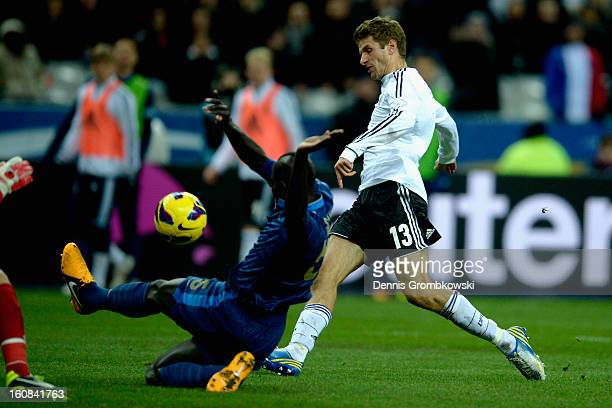 Thomas Mueller of Germany scores under the pressure of Mamadou Cabaye of France during the international friendly match between France and Germany at...