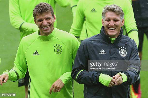 Thomas Mueller of Germany smiles with his team mate Bastian Schweinsteiger during a team Germany training session ahead of the UEFA EURO 2016 Group C...