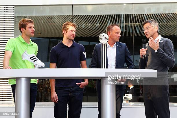 Thomas Mueller of Germany stands on stage with his brother Simon Mueller adidas PR director Oliver Brueggen and adidas CEO Herbert Hainer after...