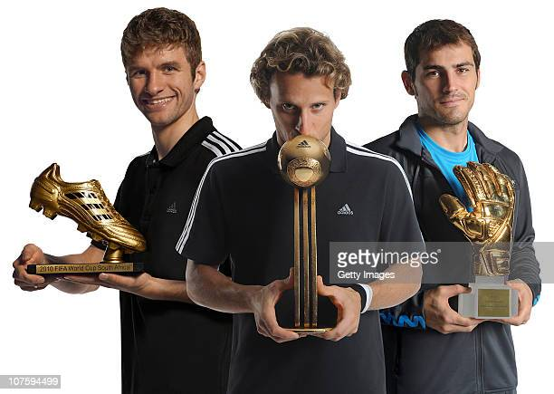 Thomas Mueller of Germany with the adidas Golden Boot Winner Trophy Diego Forlan of Uruguay with the adidas Golden Ball Winner Trophy and Iker...