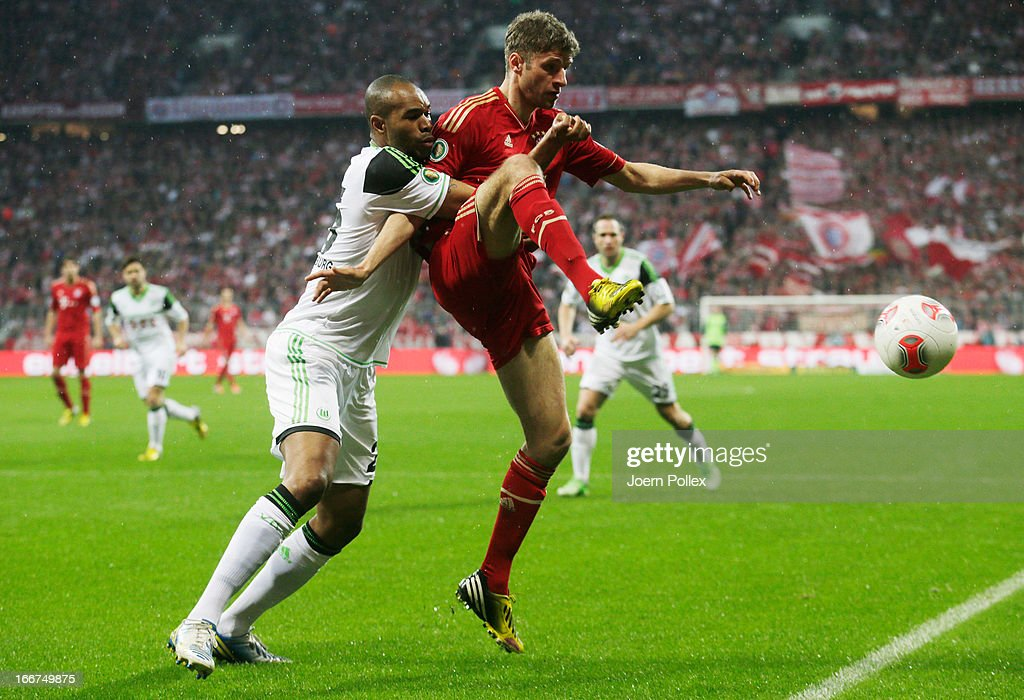 Thomas Mueller (R) of Muenchen and Naldo of Wolfsburg compete for the ball during the DFB Cup Semi Final match between Bayern Muenchen and VfL Wolfsburg at Allianz Arena on April 16, 2013 in Munich, Germany.