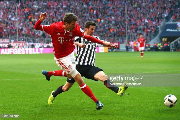 Thomas Mueller of Muenchen battles for the ball with David Abraham of Frankfurt during the Bundesliga match between Bayern Muenchen and Eintracht...