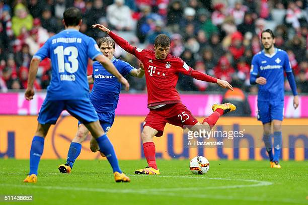 Thomas Mueller of Muenchen battles for the ball with Fabian Holland of Darmstadt during the Bundesliga match between FC Bayern Muenchen and SV...