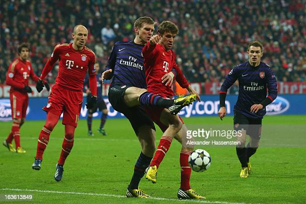 Thomas Mueller of Muenchen battles for the ball with Per Mertesacker of Arsenal FC during the UEFA Champions League Round of 16 second leg match...