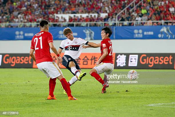 Thomas Mueller of Muenchen battles for the ball with Xuri Zhao of Guangzhou and his team mate Kim Young Gwon during the international friendly match...