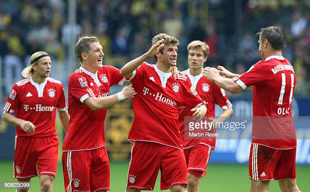 Thomas Mueller of Muenchen celebrates after scoring his team's fifth goal with team mates during the Bundesliga match between Borussia Dortmund and...
