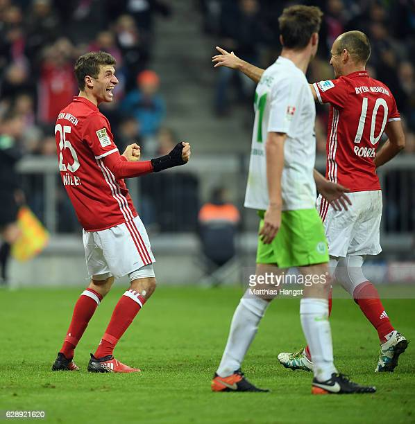 Thomas Mueller of Muenchen celebrates his team's fourth goal with team mate Arjen Robben during the Bundesliga match between Bayern Muenchen and VfL...