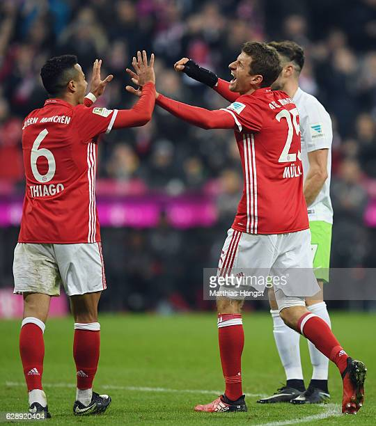 Thomas Mueller of Muenchen celebrates with Thiago Alcantara after team mate Robert Lewandowski scores his team's third goal during the Bundesliga...