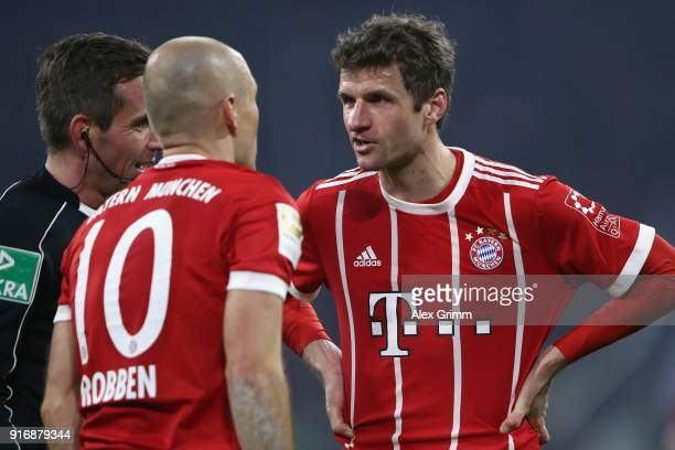 Thomas Mueller of Muenchen discusses with team mate Arjen Robben and referee Referee Tobias Stieler during the Bundesliga match between FC Bayern...