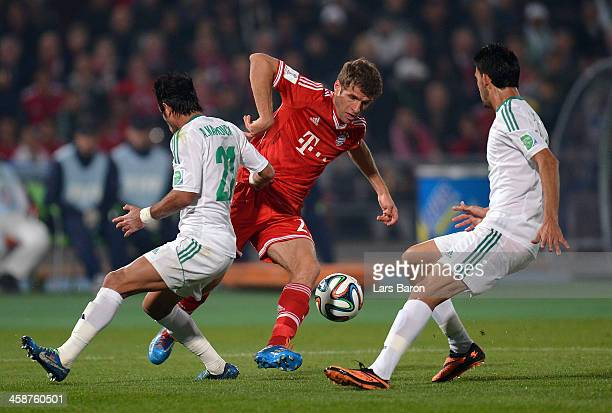 Thomas Mueller of Muenchen is challenged by Adil Karrouchy of Casablanca during the FIFA Club World Cup Final between FC Bayern Muenchen and Raja...