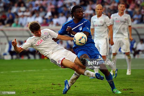 Thomas Mueller of Muenchen is challenged by Isaac Vorsah of Hoffenheim during the Bundesliga match between 1899 Hoffenheim and FC Bayern Muenchen at...