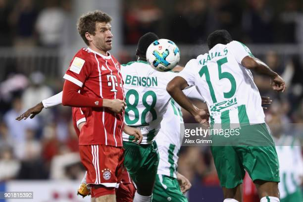 Thomas Mueller of Muenchen is challenged by John Benson and Khalil Shreff of Al Ahli during the friendly match between AlAhli and Bayern Muenchen on...