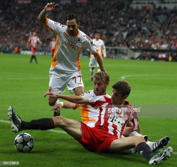 Thomas Mueller of Muenchen is challenged by Marco Cassetti and Daniele de Rossi of Roma during the UEFA Champions League group E match between FC...