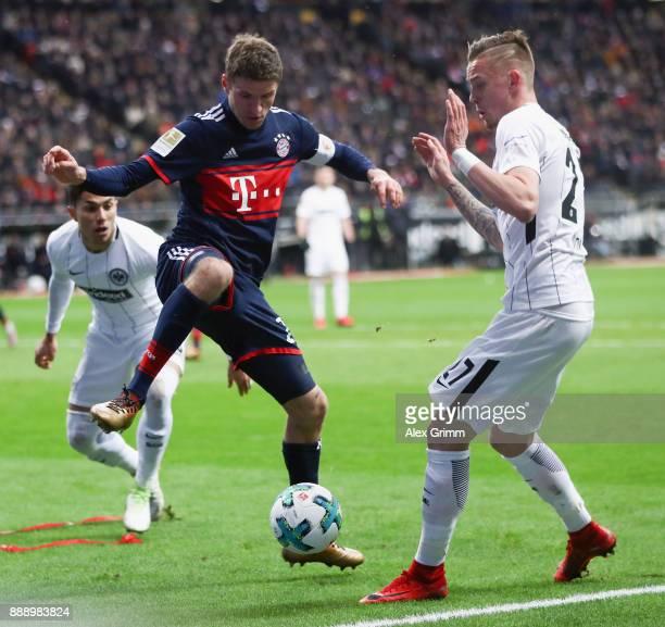 Thomas Mueller of Muenchen is challenged by Marius Wolf of Frankfurt during the Bundesliga match between Eintracht Frankfurt and FC Bayern Muenchen...