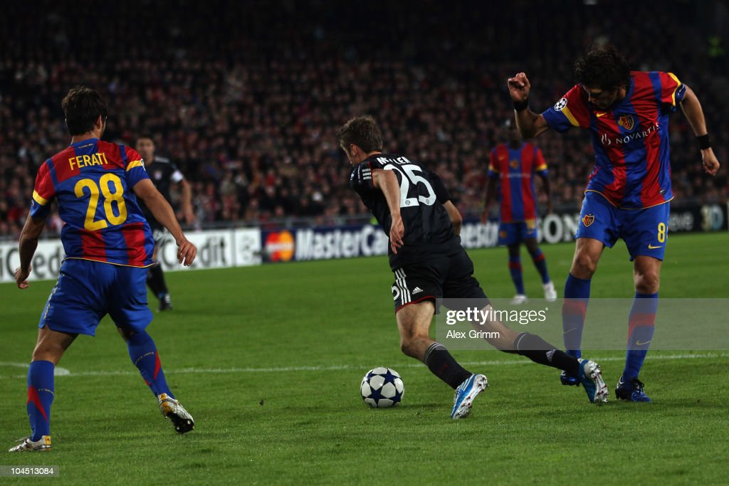 Thomas Mueller (C) of Muenchen is fouled for a penalty by Benjamin Huggel (R) of Basel during the UEFA Champions League group E match between FC Basel and FC Bayern Muenchen at the St. Jakob Park stadium on September 28, 2010 in Basel, Switzerland.
