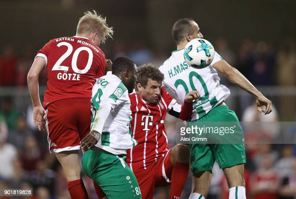 Thomas Mueller of Muenchen jumps for a header with John Benson and H Masri of Al Ahli during the friendly match between AlAhli and Bayern Muenchen on...