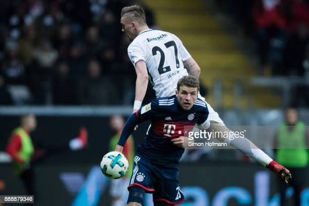 Thomas Mueller of Muenchen jumps for a header with Marius Wolf of Frankfurt during the Bundesliga match between Eintracht Frankfurt and FC Bayern...