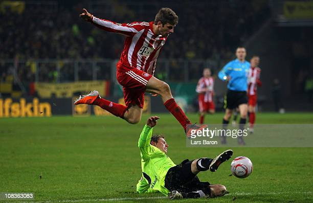 Thomas Mueller of Muenchen jumps over Tobias Feisthammel of Aachen during the DFB Cup quarter final match between Alemannia Aachen and Bayern...
