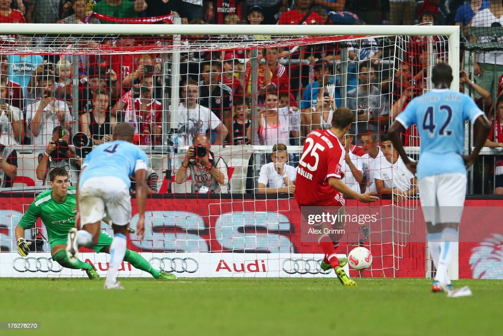 Thomas Mueller of Muenchen scores his team's first goal with a penalty against goalkeeper Costel Pantilimon of Manchester during the Audi Cup Final match between FC Bayern Muenchen and Manchester City at Allianz Arena on August 1, 2013 in Munich, Germany.