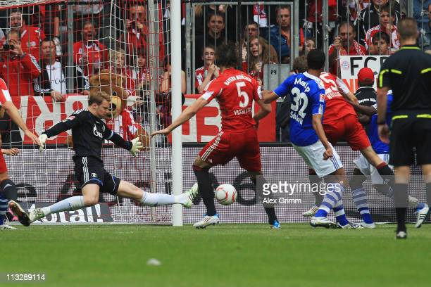 Thomas Mueller of Muenchen scores his team's second goal against goalkeeper Manuel Neuer of Schalke during the Bundesliga match between FC Bayern...