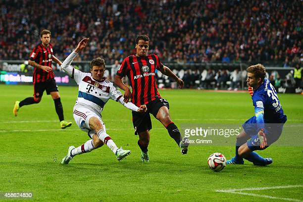 Thomas Mueller of Muenchen scores his team's third goal against Timothy Chandler and goalkeeper Felix Wiedwald of Frankfurt during the Bundesliga...