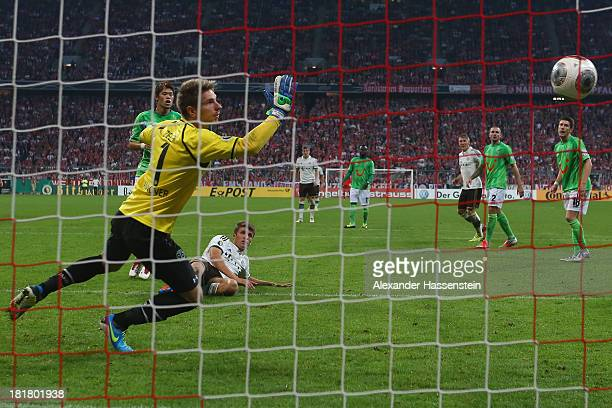 Thomas Mueller of Muenchen scores the 3rd team goal against Hiroki Sakai of Hannover and his keeper Ron-Robert Zieler during the DFB Cup match...