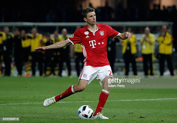 Thomas Mueller of Muenchen shoots and scores a penalty during the DFB Cup Final penalty shootout between Bayern Muenchen and Borussia Dortmund at...