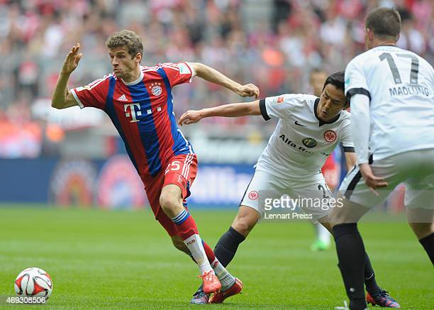 Thomas Mueller of Munich challenges Makoto Hasebe and Alexander Madlung of Frankfurt during the Bundesliga match between FC Bayern Muenchen and...