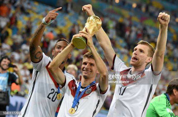 Thomas Mueller of Germany lifts up the World Cup trophy next to Jerome Boateng and Per Mertesacker after winning the FIFA World Cup 2014 final soccer...