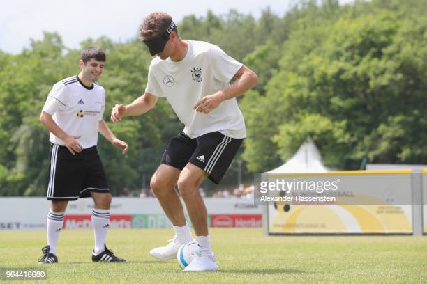Thomas Mueller plays the ball during a Blind Football demonstration match with natioanl players of the German national Blind Football team at...