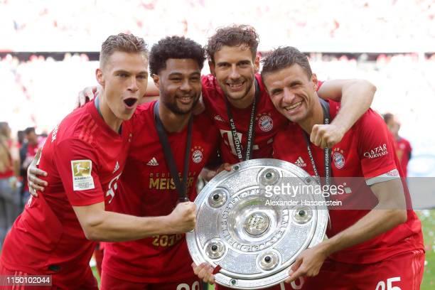 Thomas Mueller Serge Gnabry Joshua Kimmich and Leon Goretzka of FC Bayern Munich celebrate with the trophy following the Bundesliga match between FC...