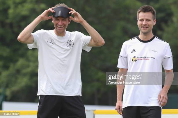 Thomas Mueller smiles with Alexander Fangmann during a Blind Football demonstration match with national players of the German national Blind Football...