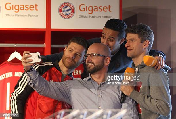 Thomas Mueller Xabi Alonso and Thiago of FC Bayern Muenchen make a photograph together with a fan during the official handover of the new Gigaset ME...