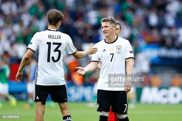 Thomas Muller and Bastian Schweinsteiger celebrate at the end of the UEFA EURO 2016 Group C match between Northern Ireland and Germany at Parc des...