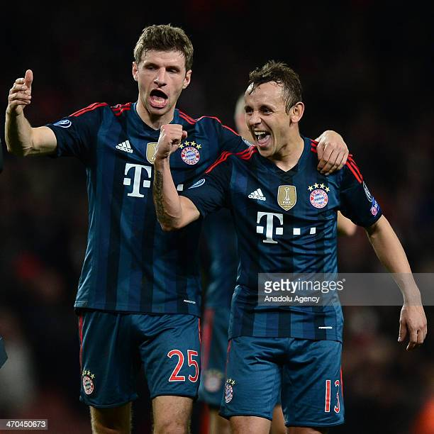 Thomas Muller and Rafinha of Bayern Munich celebrate after the final whistle during the UEFA Champions League round of 16 match between Arsenal and...