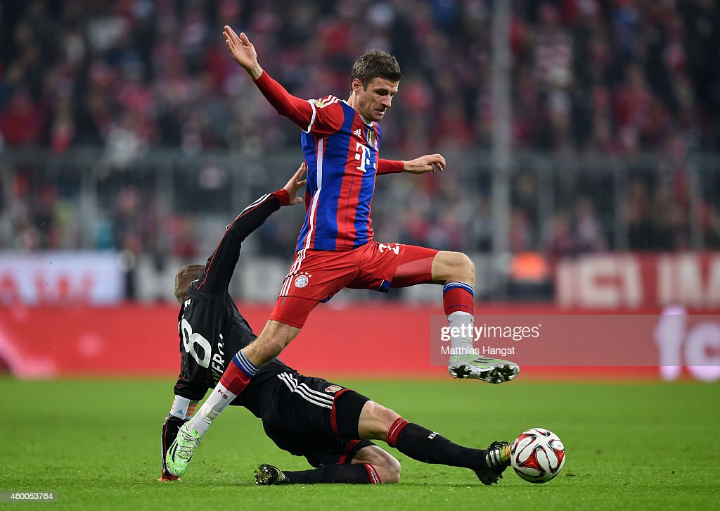 Thomas Muller of Bayern Muenchen is tackled by Lars Bender of Bayer Leverkusen during the Bundesliga match between FC Bayern Muenchen and Bayer 04 Leverkusen at the Allianz Arena on December 6, 2014 in Munich, Germany.