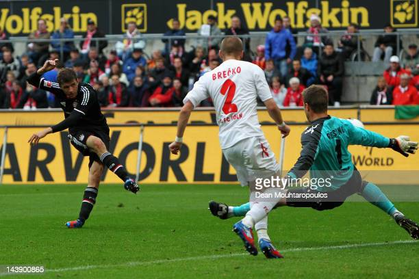 Thomas Muller of Bayern Muenchen shoots and scores the first goal of the game during the Bundesliga match between 1 FC Koeln and FC Bayern Muenchen...