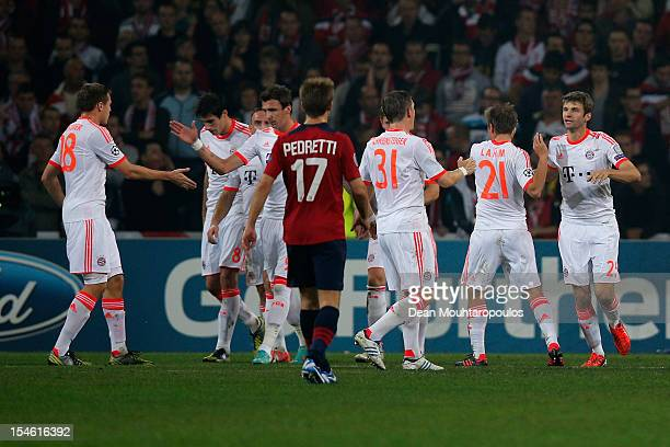 Thomas Muller of Bayern Munich celebrates scoring the first goal of the game from the penalty spot with team mates during the Group F UEFA Champions...