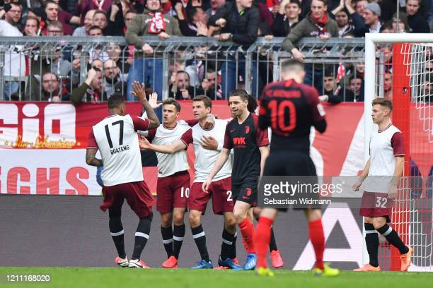 Thomas Muller of Bayern Munich celebrates with teammates Jerome Boateng, Philippe Coutinho, and Thiago Alcantara after scoring his team's first goal...