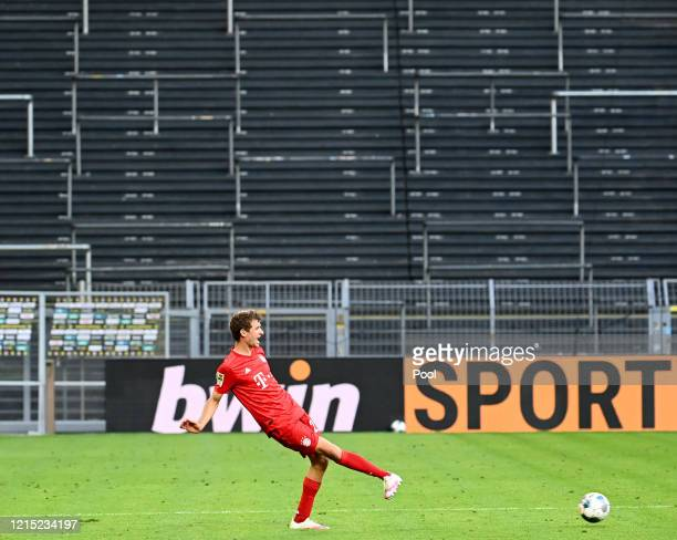 Thomas Muller of Bayern Munich passes the ball in front of a empty stand during the Bundesliga match between Borussia Dortmund and FC Bayern Muenchen...