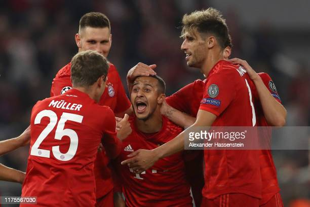 Thomas Muller of FC Bayern Munich celebrates with Thiago after scoring his sides third goal during the UEFA Champions League group B match between...