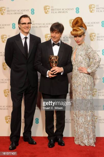 Thomas Newman winner of Original Film Music for 'Skyfall' poses in the press room with presenters David Morrissey and Paloma Faith at the EE British...