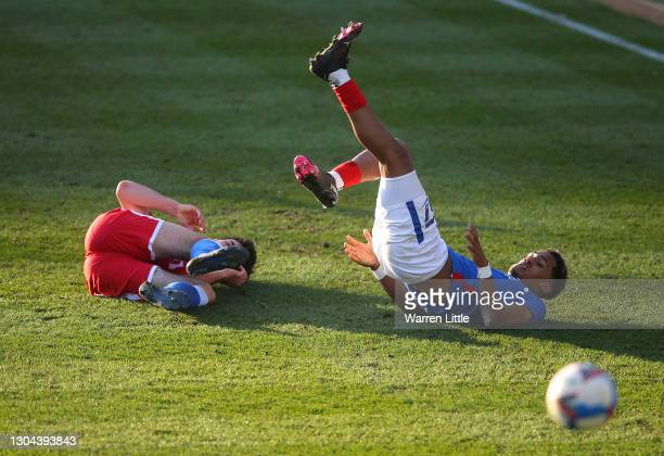 Thomas O'Connor of Gillingham FC and Haji Mnoga of Portsmouth FC both tumble on the pitch after a tackle during the Sky Bet League One match between...