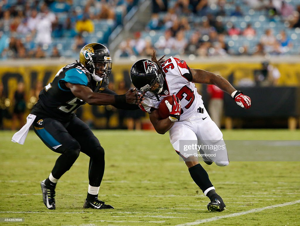J.T. Thomas #52 of the Jacksonville Jaguars attempts to tackle Devonta Freeman #33 of the Atlanta Falcons during the preseason NFL game at EverBank Field on August 28, 2014 in Jacksonville, Florida.