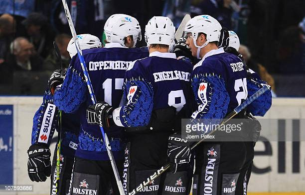 Thomas Oppenheimer of Hamburg celebrates with his team mates after scoring his team's first goal during the DEL match between Hamburg Freezers and...