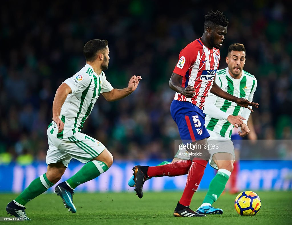 Thomas Partey af (C) being followed by Riza Durmisi of Real Betis Balompie (L) and Victor Camarasa of Real Betis Balompie (R) during the La Liga match between Real Betis and Atletico Madrid at Estadio Benito Villamarin on December 10, 2017 in Seville, .