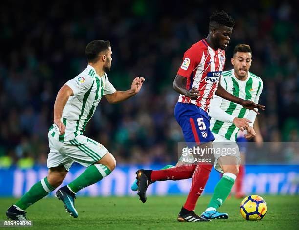 Thomas Partey af being followed by Riza Durmisi of Real Betis Balompie and Victor Camarasa of Real Betis Balompie during the La Liga match between...